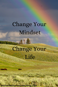 """Rainbow arching over an open field, with text, """"Change your mindset, change your life""""."""