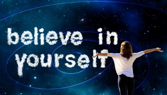 "Woman holding arms open to the universe and the words ""believe in yourself"""